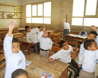 Young boys raising hands for answer question. Young boys student in classroom raising hand for answer questions in class room writing Arabic words and letters on Royalty Free Stock Image
