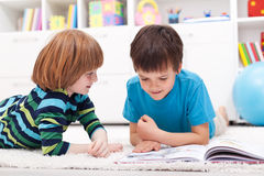 Young boys reading story book. Laying on the floor Stock Photography