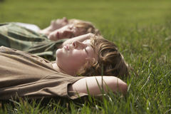 Young Boys Relaxing On Grass Stock Image