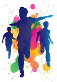 Young boys running against a paint splatter backgr Royalty Free Stock Photo