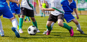 Young Boys Soccer Players Kicking Football On The Sports Field Royalty Free Stock Photography