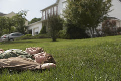 Young Boys som ligger på gräs arkivfoton
