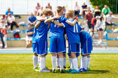 Young boys sports team on stadium. Young football players in sportswear stock photo