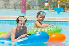 Young boys in swimming pool. Two happy young brothers playing on inflatables in swimming pool Stock Photo