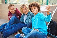 Young Boys Taking Selfie With Mobile Phone In Park Stock Photo