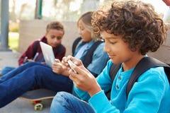 Young Boys usando las tabletas de Digitaces y los teléfonos móviles en parque Imagen de archivo