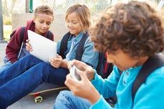 Young Boys usando las tabletas de Digitaces y los teléfonos móviles en parque Imágenes de archivo libres de regalías