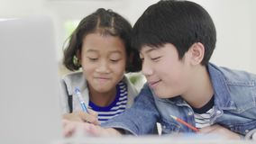 Young boys are using computers to teach and explain homework. To friends with facial expressions and happy gestures,. Dolly shoot 60fps stock video footage