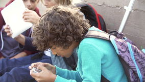 Young Boys Using Digital Tablets And Mobile Phones In Park. Group of young boys sitting by wall in playground playing games digital tablet and mobile phone.Shot stock footage