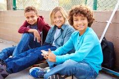Young Boys utilisant des Tablettes et des téléphones portables de Digital en parc Images stock
