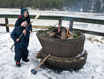 Young boys on winter picnic. Young boys baking bread on a stick outdoors over an open fire at wintertime Stock Photos