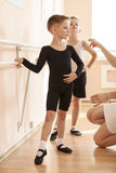 Young boys working at the barre in a ballet dance class. Teacher adjusting the position of one of them royalty free stock photos