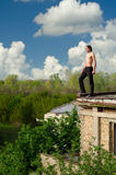 Young brave adventures man standing on roof edge of the old buil stock photos