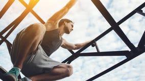 Young brave man climbing and sitting on high metal bridge royalty free stock image