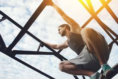 Young brave man climbing and sitting on high metal construction stock photography
