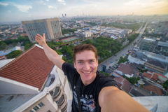 A young brave man, making a selfie on the edge of the roof of the skyscraper. Surabaya, Indonesia. A young brave man, making a salfi on the edge of the roof of a Stock Photo