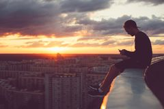 Young brave man sitting above the city with smartphone at sunset stock photography