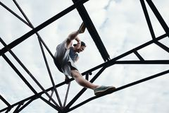 Young brave man sitting on the top of high metal construction royalty free stock photos