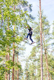 Young brave woman climbing in adventure rope park Stock Photos
