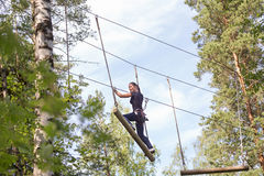 Young brave woman climbing in adventure rope park Royalty Free Stock Images
