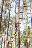 Young brave woman climbing in adventure rope park Stock Image