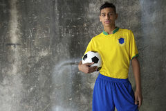 Young Brazilian Footballer in Kit Holding Football. Young Brazilian footballer in team Brazil colors kit holding soccer ball against concrete favela wall royalty free stock photo