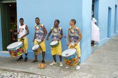 Young Brazilian Men Drumming Pelourinho Salvador. Four young Brazilian men standing on the street drumming against a blue wall in Pelourinho, Salvador, Bahia Royalty Free Stock Photo