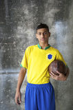 Young Brazilian Soccer Player in Uniform Holding Football Royalty Free Stock Photography