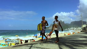 Young Brazilians Walk with Boogie Boards Rio de Janeiro Brazil. RIO DE JANEIRO, BRAZIL - MARCH 1, 2015: Young Brazilians walk with boogie boards looking at the stock video