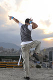 Young break dancer on top of the building. Young break dancer dancing on top of the building with blured cityscape and sunset in background Royalty Free Stock Images