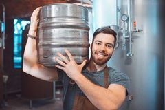 A young brewer in an apron holds a barrel with beer in the hands stock photo