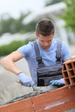 Young brick layer apprentice at work. Young brick layer working outside on brick wall construction Stock Photos