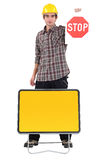 Young bricklayer holding stop sign Stock Photo