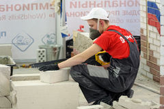 Young bricklayer performs a task of competition Stock Photos