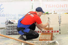 Young bricklayer performs a task of competition Royalty Free Stock Photo