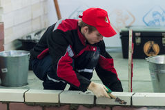 Young bricklayer performs a task of competition Stock Images