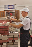 Young bricklayer performs a task of competition Royalty Free Stock Image
