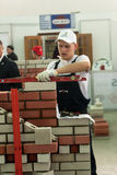 Young bricklayer performs a task of competition Stock Photography
