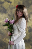 Young Bride. Beautiful young bride smiling and holding a bouquet of Star Gazer Lillies Royalty Free Stock Images