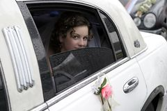 Young bride. The young bride in a veil looks out of a window of a limousine on the groom Stock Photo