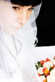 Young bride. In wedding wear with bouquet of roses sitting in the car stock photo