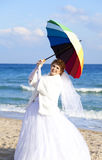 Young bride on the beach with umbrella Stock Images