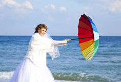 Young bride on the beach with umbrella Royalty Free Stock Photos