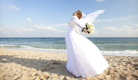 Young bride on the beach wqith flowers Stock Photography