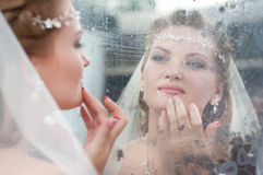 Young bride. The young beautiful bride checks a make-up and jewelry, looking in a mirror royalty free stock photo