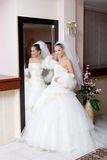 A young bride in a beautiful dress by a big mirror Stock Photo