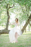 Young bride in beautiful wedding dress sitting on tree outdoors Royalty Free Stock Photography