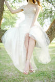 Young bride in beautiful wedding dress sitting on tree outdoors Stock Image