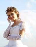 Young bride at blue sky background Royalty Free Stock Photos