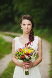 Young bride with bouquet of flowers in her hands Royalty Free Stock Image
